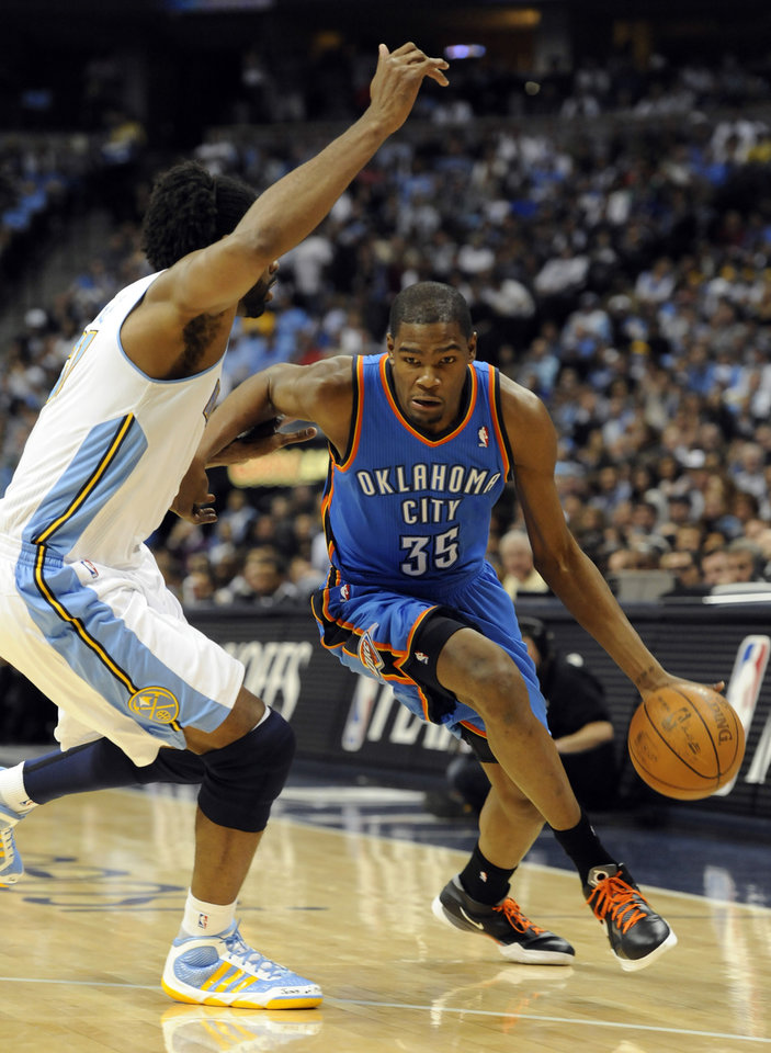Oklahoma City Thunder forward Kevin Durant (35) drives past Denver Nuggets center Nene (31) from Brazil during the first half of game 3 of a first-round NBA basketball playoff series Saturday, April 23, 2011, in Denver. (AP Photo/Jack Dempsey)