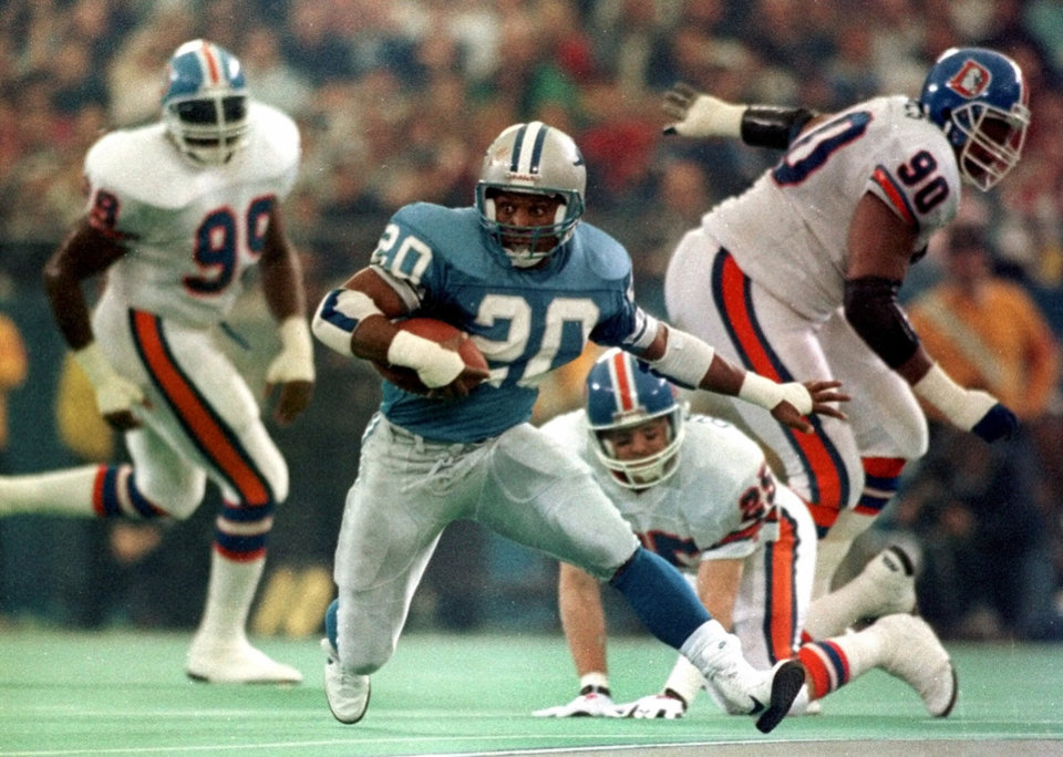 Photo - ** FILE **   NFL FOOTBALL: Detroit Lions running back Barry Sanders leaves behind Denver Broncos defenders in 1990 at the Pontiac Silverdome in Pontiac, Mich.  Sanders made the Pro Football Hall of Fame on his first attempt Saturday, Jan. 31, 2004, making it look as easy as everything else he did in his spectacular career. (AP Photo/Duane Burleson, file)
