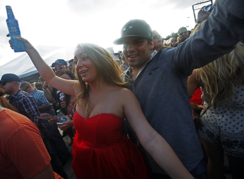 Photo - Sierra Swanda and Kurtis Kuryk dance together as the Casey Donahew Band performs at OKC Fest in downtown Oklahoma City on Friday, June 27, 2014. OKC Fest is a new two day country music festival with multiple stages downtown. Photos by KT King/The Oklahoman