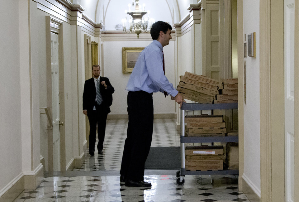 Photo - A trolly loaded with pizza is wheeled onto the elevator that serves the office of House Speaker John Boehner of Ohio, on Capitol Hill, Tuesday, Oct. 15, 2013, in Washington. The partial government shutdown is in its third week and less than two days before the Treasury Department says it will be unable to borrow and will rely on a cash cushion to pay the country's bills. (AP Photo/Carolyn Kaster)