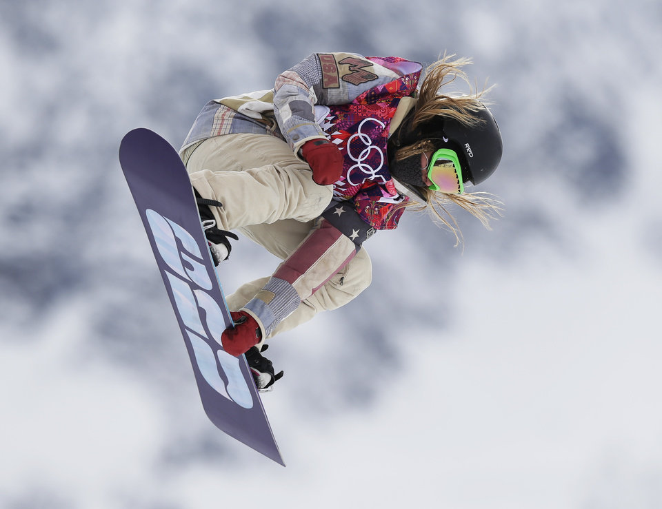 Photo - Jamie Anderson of the United States takes a jump on her first run in the women's snowboard slopestyle final at the 2014 Winter Olympics, Sunday, Feb. 9, 2014, in Krasnaya Polyana, Russia.  (AP Photo/Andy Wong)