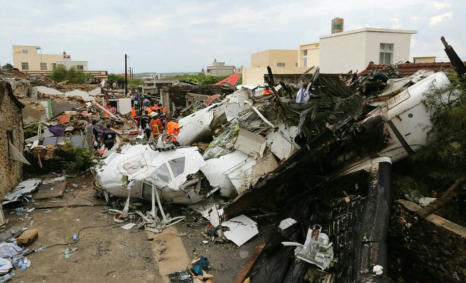 Photo - Rescue workers survey the wreckage of TransAsia Airways Flight GE222 on the Taiwanese island of Penghu Thursday, July 24, 2014. The plane attempting to land in stormy weather crashed on the island late Wednesday, killing more than 40 people and wrecking houses and cars on the ground. (AP Photo) TAIWAN OUT