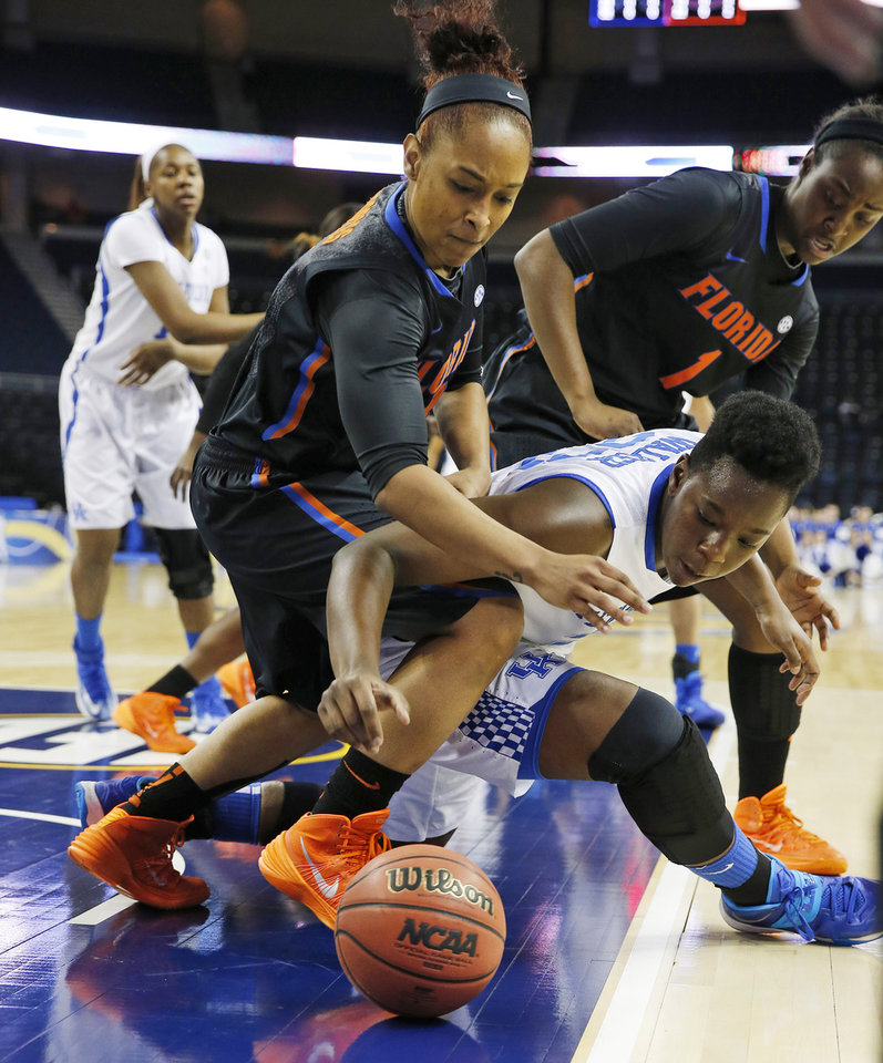 Photo - Florida guard Cassie Peoples (13) and Kentucky forward/center Samarie Walker (23) fight for a loose ball in the first half of a quarterfinal women's Southeastern Conference tournament NCAA college basketball game Friday, March 7, 2014, in Duluth, Ga.   (AP Photo/John Bazemore)