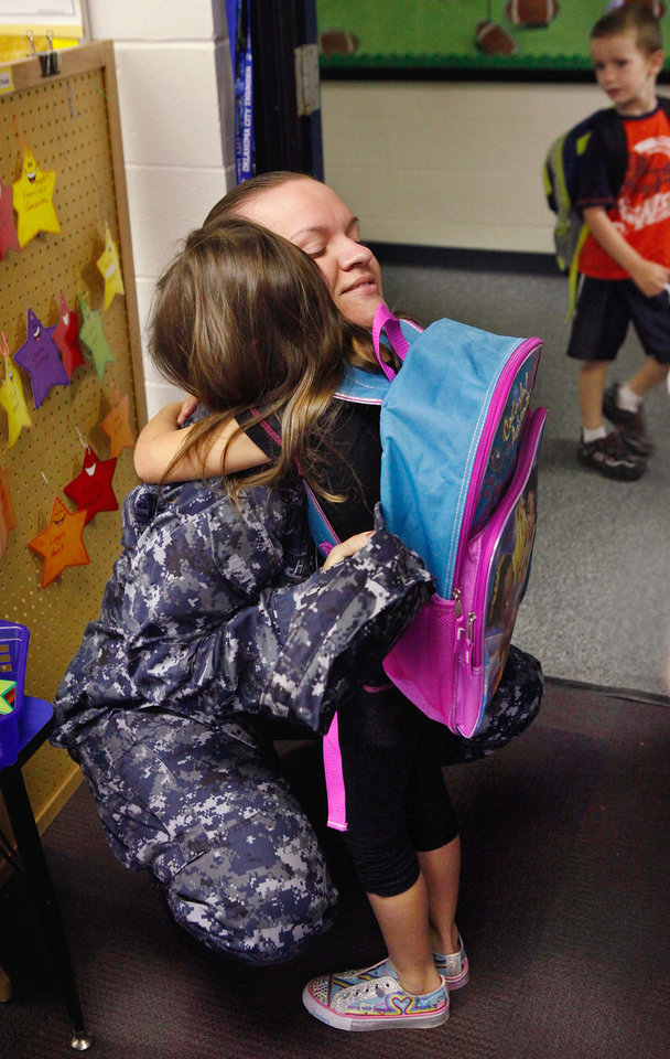 Photo - Petty Officer Second Class Sara Harper (US Navy) gets a hug from daughter, Kiley, 5, before leaving her with her kindergarten classmates at Tinker Elementary School  Friday morning, Aug. 19, 2011.      by Jim Beckel, The Oklahoman.  ORG XMIT: KOD