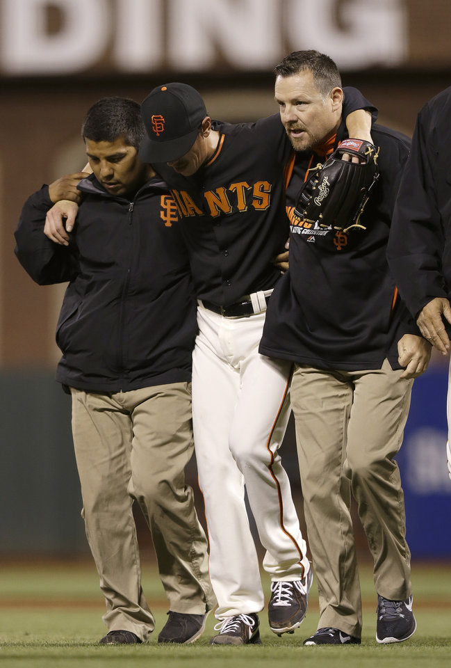 Photo - San Francisco Giants pitcher Tim Lincecum, center, is helped off the field by trainers after being struck by a ball hit by Oakland Athletics' Daric Barton during the fourth inning of an exhibition baseball game in San Francisco, Friday, March 28, 2014. (AP Photo/Jeff Chiu)