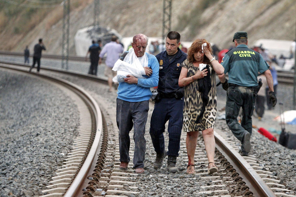 Photo - In this photo taken on Wednesday July 24 2013, Wounded people are evacuated at the site of a train accident in Santiago de Compostela, Spain. Spanish police on Friday detained the driver of a train that crashed in northwestern Spain, lowered the death toll from 80 to 78 and took possession of the