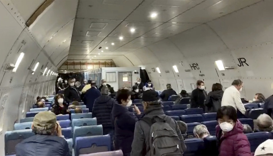Photo -  In this image from a video taken on Monday, Feb. 17, 2020, U.S. passengers who evacuated off the quarantined cruise ship the Diamond Princess,   board a Kalitta Air plane bound for the U.S., at Haneda airport in Tokyo.(Cheryl and Paul Molesky via AP)