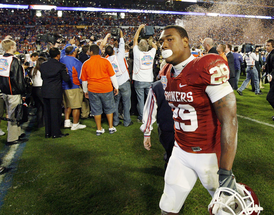 Photo - OU's Chris Brown (29) walks off the field as photographers swarm Florida players after the BCS National Championship college football game between the University of Oklahoma Sooners (OU) and the University of Florida Gators (UF) on Thursday, Jan. 8, 2009, at Dolphin Stadium in Miami Gardens, Fla. The Florida Gators won, 24-14. PHOTO BY NATE BILLINGS, THE OKLAHOMAN