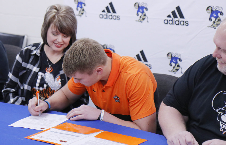 Photo - Jeff Roberson, Choctaw, signs with OSU, as mother DeeDee Devine and father Aaron Roberson, look on, during National Signing Day for high school football players, Wednesday, December 18, 2019. [Photo by Doug Hoke/The Oklahoman]