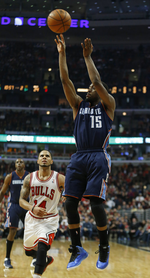 Photo - Charlotte Bobcats guard Kemba Walker, right, shoots against Chicago Bulls guard D.J. Augustin, center, during the first half of an NBA basketball game in Chicago, Saturday, Jan. 11, 2014. (AP Photo/Kamil Krzaczynski)