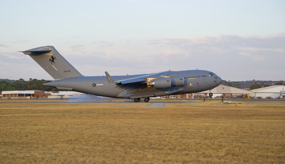 Photo - In this Friday, March 28, 2014 photo released by the Australian Defence, a Royal Australian Air Force C-17 Globemaster arrives to help with the search for the missing Malaysia Airlines Flight 370 at RAAF Pearce Base in Perth, Australia. Objects spotted floating in a new search area for debris from the missing Malaysian jetliner need to be recovered and inspected before they can be linked to the plane, Australian officials said Saturday. Eight planes were ready to comb the newly targeted area off the west coast of Australia after several objects were spotted Friday, including two rectangular items that were blue and gray, and ships on the scene will attempt to recover them, the Australian Maritime Safety Authority said. (AP Photo/Australian Defence, Justin Brown)