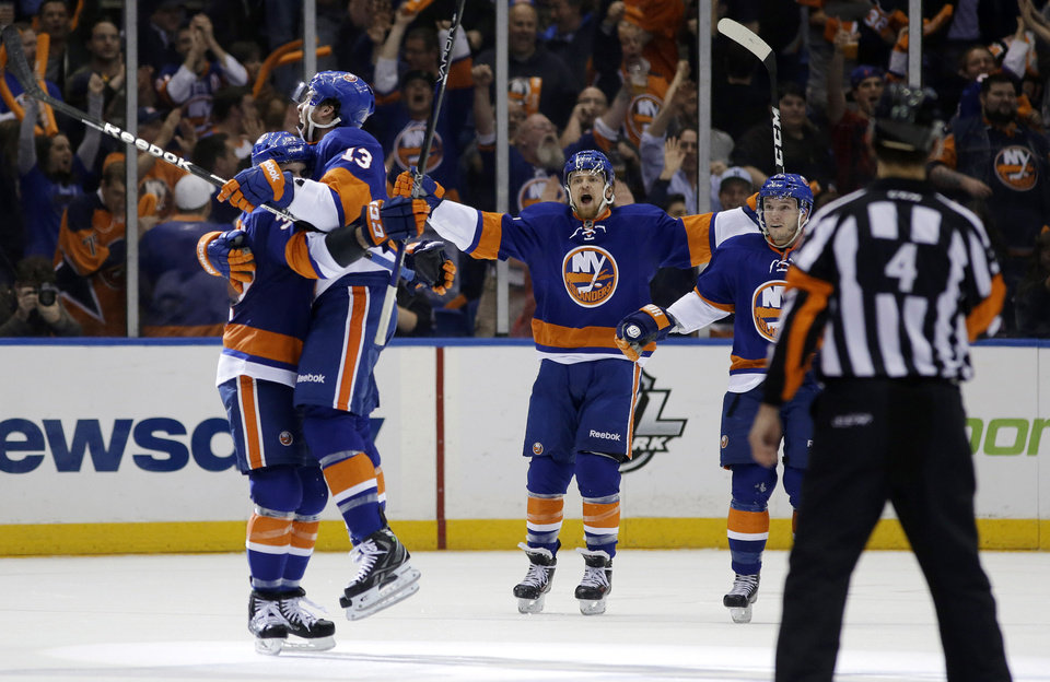 Photo - New York Islanders defenseman Brian Strait (37) lifts up New York Islanders right wing Colin McDonald (13) after McDonald scored against the Pittsburgh Penguins in the first period of Game 6 of a first-round NHL Stanley Cup playoff hockey series in Uniondale, N.Y., Saturday, May 11, 2013. (AP Photo/Kathy Willens)