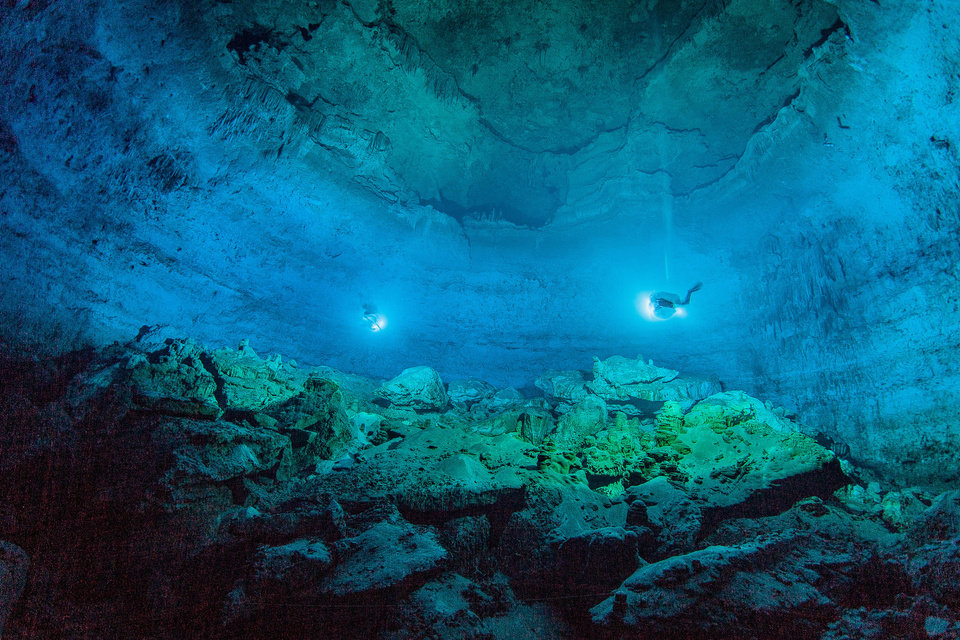 Photo - In this undated photo made available by Roberto Chavez Arce in May 2014, divers use lights to illuminate Hoyo Negro, an underwater cave in Mexico's Yucatan Peninsula where the remains of
