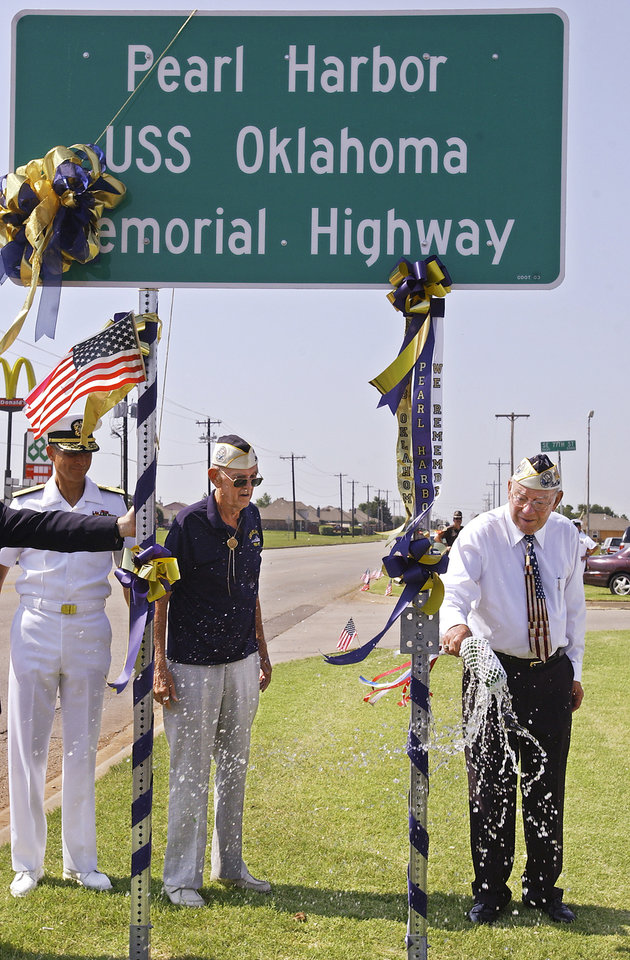 "Oklahoma City, Thursday, 7/3/03. Dedication ceremony of the ""Pearl Harbor/Uss Oklahoma Memorial Highway"" (Sooner Road south of I240). Pearl Harbor survivors Paul Goodyear and Doc Stanley, braking a champagne bottle on the sign, to dedicate the highway.  Staff photo by David McDaniel."