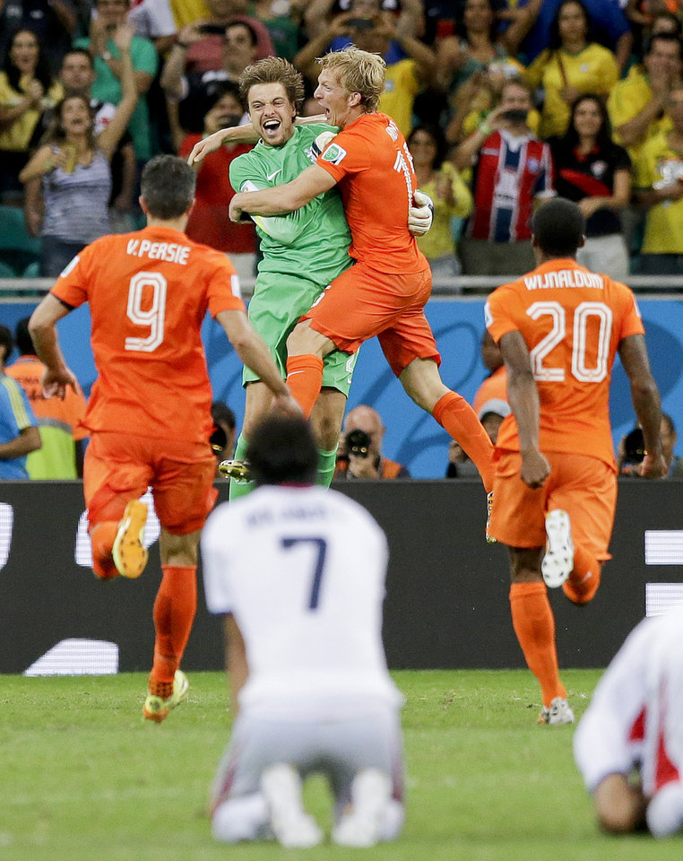 Photo - Netherlands' goalkeeper Tim Krul, center left, celebrates after making the final save in a penalty shoot out during the World Cup quarterfinal soccer match between the Netherlands and Costa Rica at the Arena Fonte Nova in Salvador, Brazil, Saturday, July 5, 2014. The Netherlands won 4-3 0n penalties after the match ended 0-0 after extra time. (AP Photo/Matt Dunham)