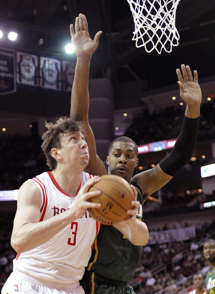 Photo - Houston Rockets's Omer Asik (3) is pressured by Utah Jazz's Derrick Favors as he goes to the basket in the first half of an NBA basketball game Monday, March 17, 2014, in Houston. (AP Photo/Pat Sullivan)