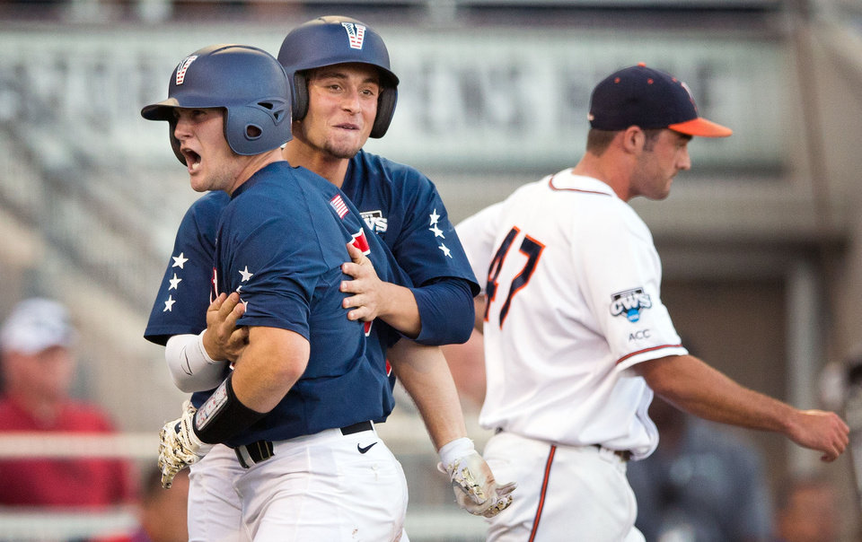 Photo - Vanderbilt's Jason Delay, left, and Rhett Wiseman celebrate after they scored on Tyler Campbell's double that scored three runs in the 9-run third inning. UVA relief pitcher Whit Mayberry (47) is at right. The University of Virginia played a baseball game against Vanderbilt in the first game of the championship finals of the College World Series at TD Ameritrade Park in Omaha, Neb., on Monday, June 23, 2014. (AP Photo/The World-Herald, Ryan Soderlin) MAGS OUT TV OUT