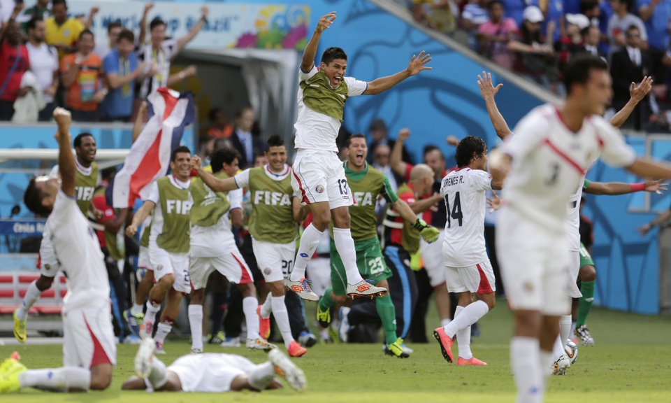 Photo - Costa Rican players come off their bench to celebrate their 1-0 victory over Italy during the group D World Cup soccer match between Italy and Costa Rica at the Arena Pernambuco in Recife, Brazil, Friday, June 20, 2014.  (AP Photo/Petr David Josek)