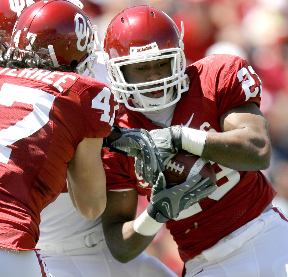 Photo - OU's Jermie Calhoun is hit during Oklahoma's Red-White football game at The Gaylord Family - Oklahoma Memorial Stadiumin Norman, Okla., Saturday, April 11, 2009. Photo by Bryan Terry, The Oklahoman