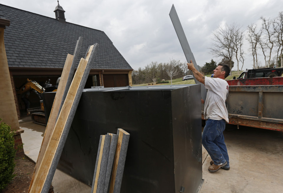 Photo - Robert Ozment, with Smart Shelters Inc., unloads parts to a storm shelter at Patrick and Kim Lenow's home. Photo by Bryan Terry, The Oklahoman