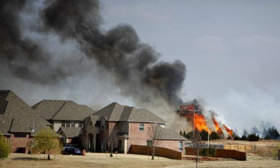 Photo - A grass fire approaches homes in a neighborhood near South County Line Road and S.W. 29th, Sunday, March 20, 2011, in Mustang, Okla.. Photo by Sarah Phipps, The Oklahoman