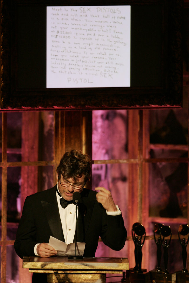 Photo - FILE- In this March 13, 2006 file photo, Jann Wenner, vice chairman of the Rock & Roll Hall of Fame board of directors, reads a letter from the Sex Pistols refusing to attend their own induction into the Rock & Roll Hall of Fame during ceremonies, in New York.  The British band, which featured lead singer Johnny Rotten and late bassist Sid Vicious, said in a hand-written note posted on its website that the hall was like