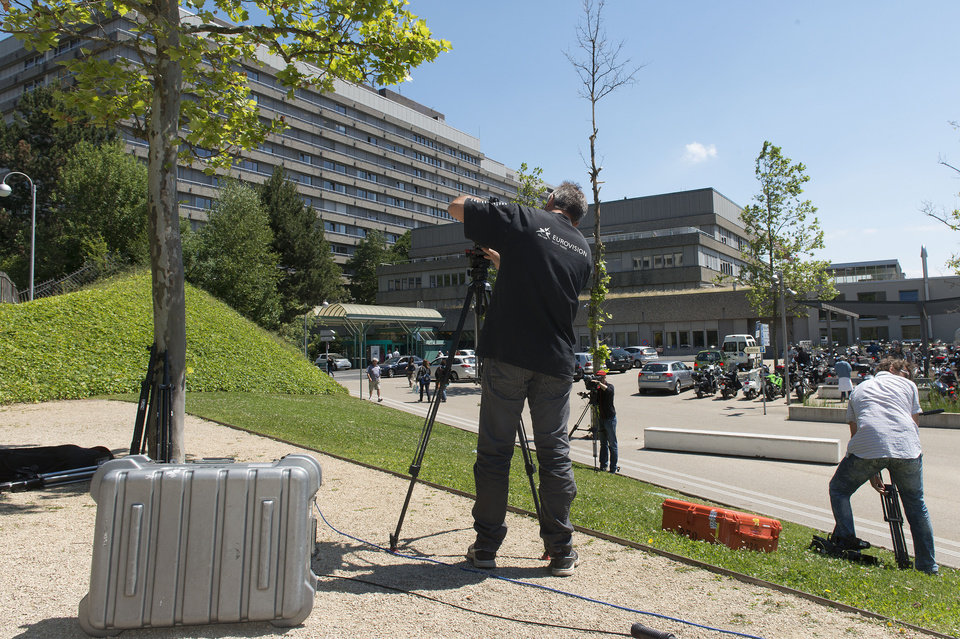 Photo - Media stand in front of the Lausanne University Hospital (the ''CHUV'') in Lausanne, Switzerland, Monday, June 16, 2014. Former German Formula One driver Michael Schumacher is no longer in a coma and has left a French hospital where he had been receiving treatment since a skiing accident in December, but has been transferred to the Lausanne University Hospital his manager said Monday, June 16 2014. (AP Photo/Keystone, Sandro Campardo)