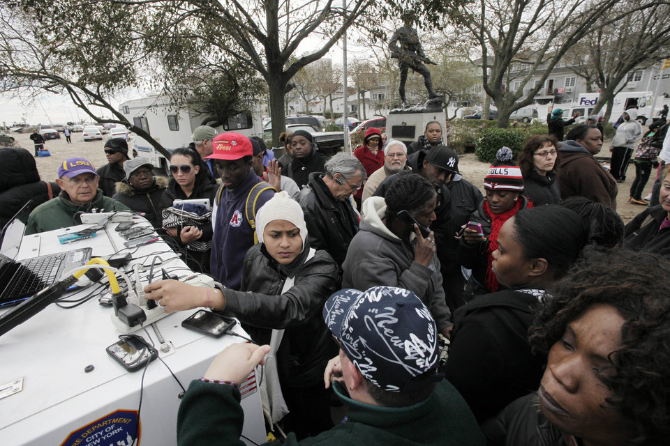 Photo - Residents of the oceanside community of Far Rockaway, New York, crowd around a portable generator to charge cell phones and laptops, Thursday, Nov. 1, 2012.    Hundreds of thousands in New York City alone were still without power Thursday, especially in Lower Manhattan, which remained in the dark roughly south of the Empire State Building after floodwaters had knocked out power. (AP Photo/Mark Lennihan) ORG XMIT: NYML131