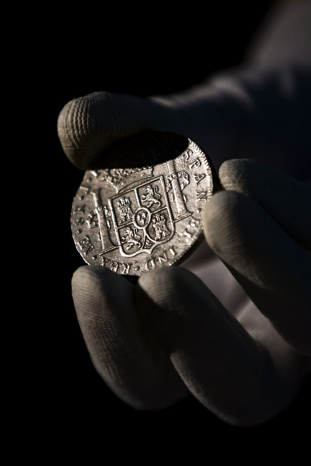 A worker of the ministry holds up for photographers a silver coin from the shipwreck of a 1804 galleon, on its first display to the media at a ministry building, in Madrid, Friday, Nov. 30, 2012. Spanish cultural officials have allowed the first peep at 16 tons (14.5 metric tons) of the shipwreck, \'Nuestra Senora de las Mercedes\' a treasure worth an estimated $500 million that a U.S. salvage company gave up after a five-year international ownership dispute. (AP Photo/Daniel Ochoa de Olza)