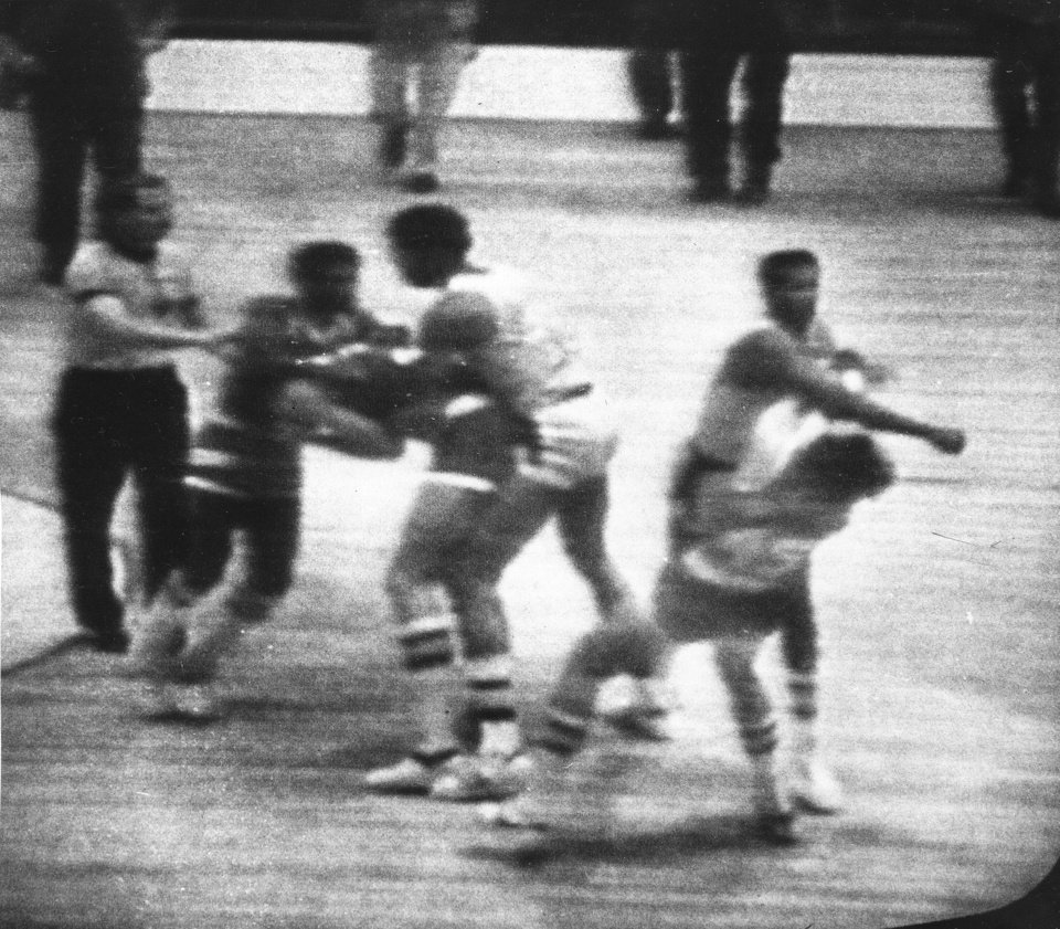 Photo - FILE - In this Dec. 9, 1977, file image made from a television frame, Los Angeles Lakers' Kermit Washington, right, throws a punch to the jaw of Houston Rockets' Rudy Tomjanovich during an NBA basketball game in Los Angeles. Lakers and Rockets players scuffle at left as an official steps in to separate them. Tomjanovich was hospitalized from the injuries suffered from the blow. The hit was speculated to stand among the worst in league history. (AP Photo/NBC-TV, File) ORG XMIT: NY152