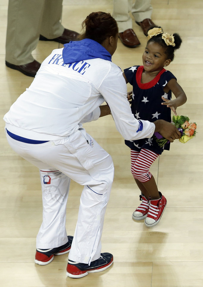Lailaa Williams, the 3-year-old daughter of United States\' player Candace Parker, runs towards France\'s Sandrine Gruda after the medal ceremony for the women\'s gold medal basketball game at the 2012 Summer Olympics, Saturday, Aug. 11, 2012, in London. (AP Photo/Victor R. Caivano)