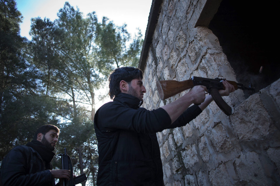 Photo - A Free Syrian Army fighter fires his machine gun toward Syrian Army positions during an assault on a military base in Tal Sheen, Syria, Saturday, Dec 15, 2012 (AP Photo / Manu Brabo)