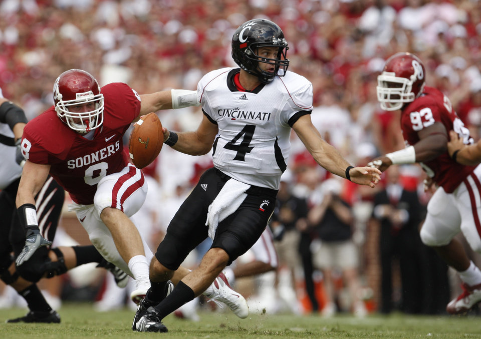 Photo - OU: Cincinnati quarterback Dustin Grutza, center, is chased by University of Oklahoma defenders Ryan Reynolds, left, and Gerald McCoy, right, in the first quarter of an NCAA college football game in Norman, Okla., Saturday, Sept. 6, 2008. (AP Photo/Sue Ogrocki)