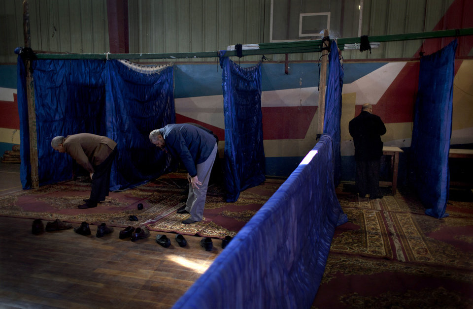 Photo - An Egyptian man votes while other voters perform the noon prayers at gymnasium hall used as a polling station during the second round of a referendum on a disputed constitution drafted by Islamist supporters of president Mohammed Morsi, in Giza, Egypt, Saturday, Dec. 22, 2012. (AP Photo/Nasser Nasser)