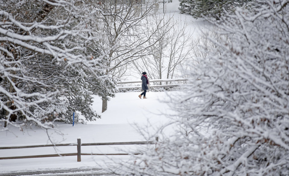 Photo - A person walks on snow covered trails at Hafer Park following a winter storm in Edmond, Okla., Wednesday, Feb. 5, 2020.  [Sarah Phipps/The Oklahoman]