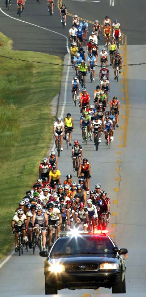 Photo -  Police escort riders traveling east on Robinson Street during the annual Norman Conquest bike ride. PHOTO BY STEVE SISNEY, THE OKLAHOMAN   STEVE SISNEY
