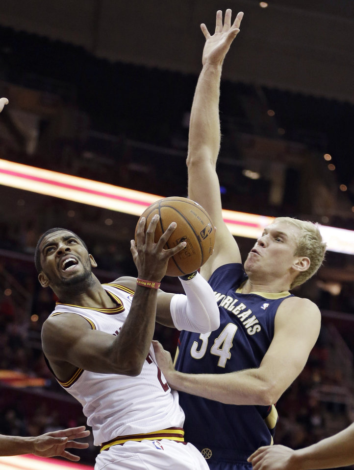 Photo - Cleveland Cavaliers' Kyrie Irving, left, shoots over New Orleans Pelicans' Greg Stiemsma, right, during the second quarter of an NBA basketball game, Tuesday, Jan. 28, 2014, in Cleveland. (AP Photo/Tony Dejak)