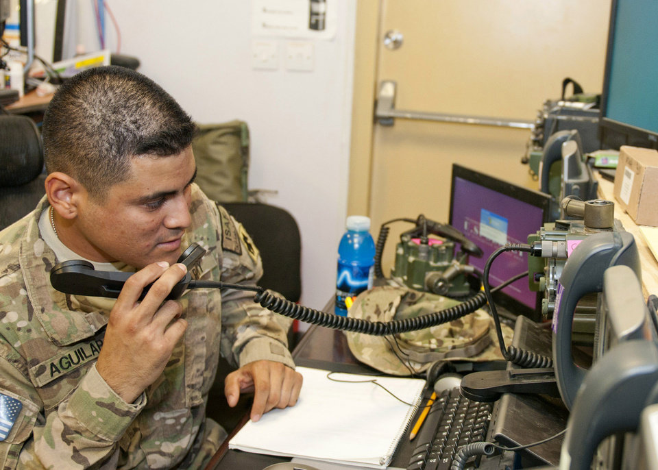 MILITARY: Spc. Joel Aguilar of Oklahoma City, Okla., with Headquarters, Headquarters Company, 45th Infantry Brigade Combat Team speaks on one of several radios in the Tactical Operations Center July 16, at Forward Operating Base Gamberi, Afghanistan. The radios are used to communicate with units throughout the 45th IBCT's area of operation. (Photo by Spc. Leslie Goble, Task Force Thunderbird Public Affairs Office)