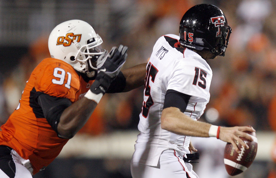 Photo - OSU's Ugo Chinasa (91) gets a hand on Taylor Potts (15) of Texas Tech during the second half of the college football game between Oklahoma State University (OSU) and Texas Tech University at Boone Pickens Stadium in Stillwater, Okla. Saturday, Nov. 14, 2009. Photo by Sarah Phipps, The Oklahoman
