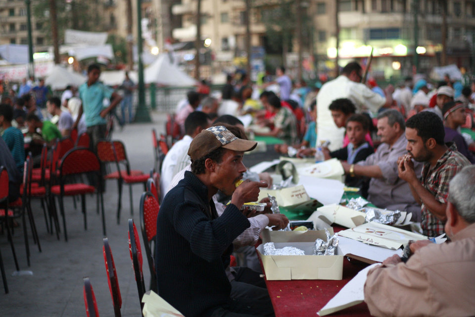 Photo - Egyptians break their fast during the first day of Ramadan outside Tahrir Square in Cairo, Egypt, Wednesday, July 10, 2013. After a week of violence and mass demonstrations, Egyptians were hoping that Wednesday's start of the Muslim holy month of Ramadan will significantly calm the streets. The sunrise-to-sunset fast cuts down on daytime activity, although there are fears of unrest at night.(AP Photo/Nasser Shiyoukhi)