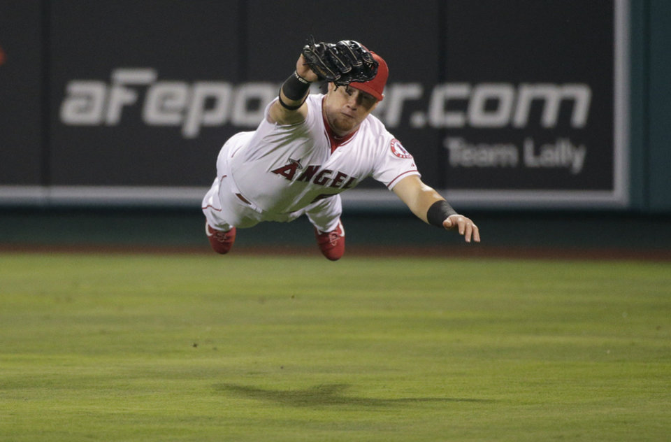 Photo - Los Angeles Angels right fielder Kole Calhoun catches a ball hit by Los Angeles Dodgers' Matt Kemp during the eighth inning of a baseball game Wednesday, Aug. 6, 2014, in Anaheim, Calif. (AP Photo/Jae C. Hong)