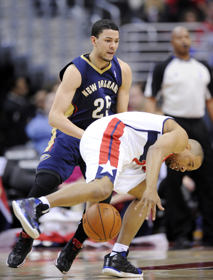 Photo - Washington Wizards guard Andre Miller, front, tries to get the ball against New Orleans Pelicans guard Austin Rivers (25) during the first half of an NBA basketball game Saturday, Feb. 22, 2014, in Washington. (AP Photo/Nick Wass)