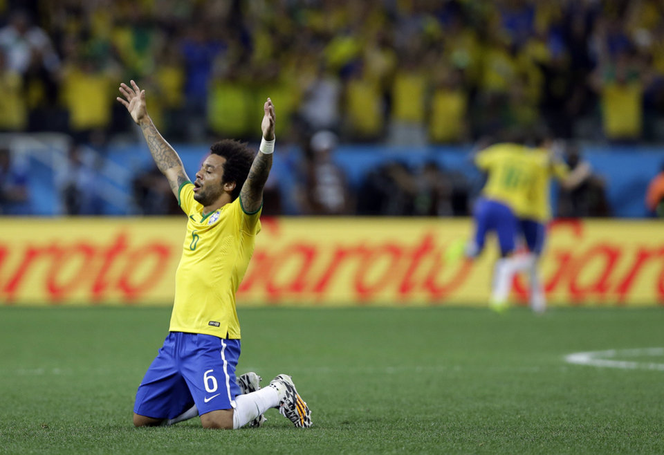Photo - Brazil's Marcelo celebrates after his teammate Oscar scored his sides 3rd goal during the group A World Cup soccer match between Brazil and Croatia, the opening game of the tournament, in the Itaquerao Stadium in Sao Paulo, Brazil, Thursday, June 12, 2014.  (AP Photo/Kirsty Wigglesworth)