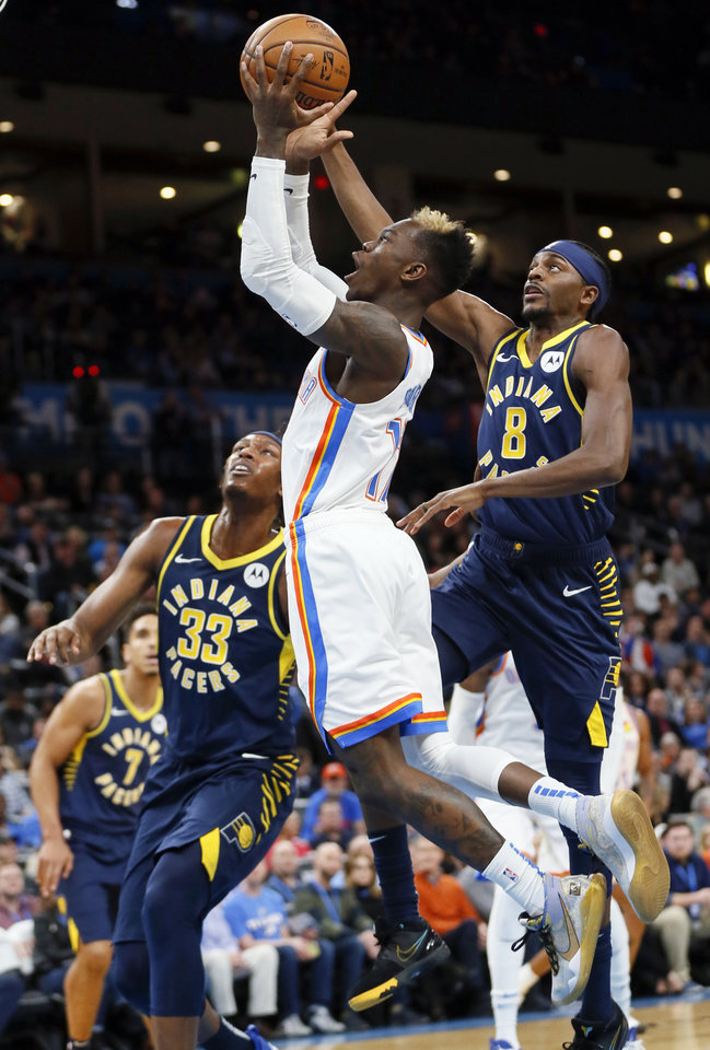 Photo - Oklahoma City's Dennis Schroder (17) takes the ball to the basket next to Indiana's Myles Turner (33) and Justin Holiday (8) in the first quarter during an NBA basketball game between the Indiana Pacers and the Oklahoma City Thunder at Chesapeake Energy Arena in Oklahoma City, Wednesday, Dec. 4, 2019. [Nate Billings/The Oklahoman]