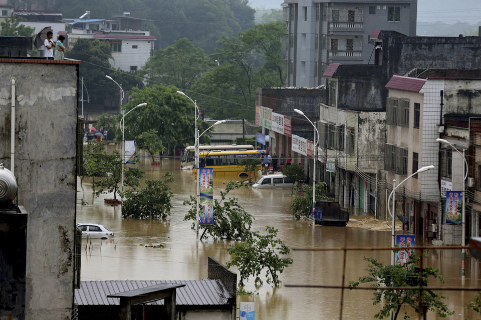 Photo - In this photo released by China's Xinhua News Agency taken on Thursday, May 22, 2014, roads and buildings are flooded after a rainstorm in Qigong Township in Yangshan County in Qingyuan City, south China's Guangdong Province. The Chinese state news agency is reporting 12 people have died in widespread flooding in southern China.  Xinhua News Agency said the flooding affected 649,000 people in Qingyuan city in Guangdong province as of Saturday afternoon, May 24, 2014, with 3,300 houses collapsing. (AP Photo/Xinhua, Li Zuomiao) NO SALES
