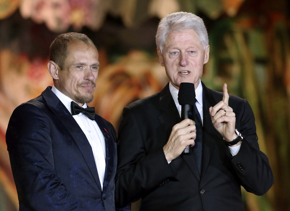 Photo - Former U.S. President Bill Clinton, right, delivers a speech next to Gery Keszler, left, organizer and founder of the Life Ball during the opening ceremony of the Life Ball in front of City Hall in Vienna, Austria, Saturday, May 31, 2014. The Life Ball is a charity gala to raise money for people living with HIV and AIDS. (AP Photo/Ronald Zak)