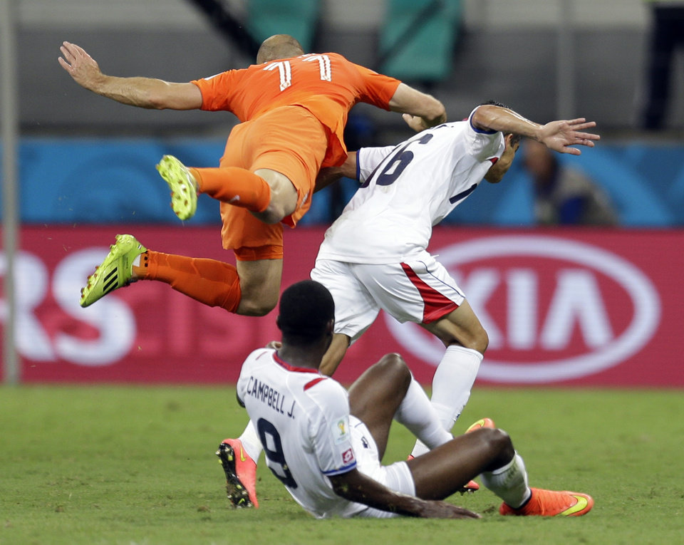 Photo - Netherlands' Arjen Robben falls over Costa Rica's Cristian Gamboa (16) after heading the ball during the World Cup quarterfinal soccer match at the Arena Fonte Nova in Salvador, Brazil, Saturday, July 5, 2014. (AP Photo/Natacha Pisarenko)