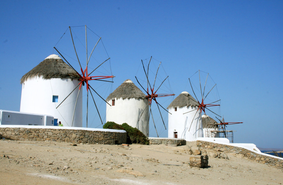 Photo - This July 6, 2014 photo shows picturesque windmills on the island of Mykonos in the Cyclades, a Greek island chain in the Aegean Sea. The tradition of building windmills on the island dates back centuries. The Cyclades are known for panoramic views of the sea, homes tucked into cliffsides and waterfronts, black-sand beaches and dramatic sunsets. (AP Photo/Kristi Eaton)