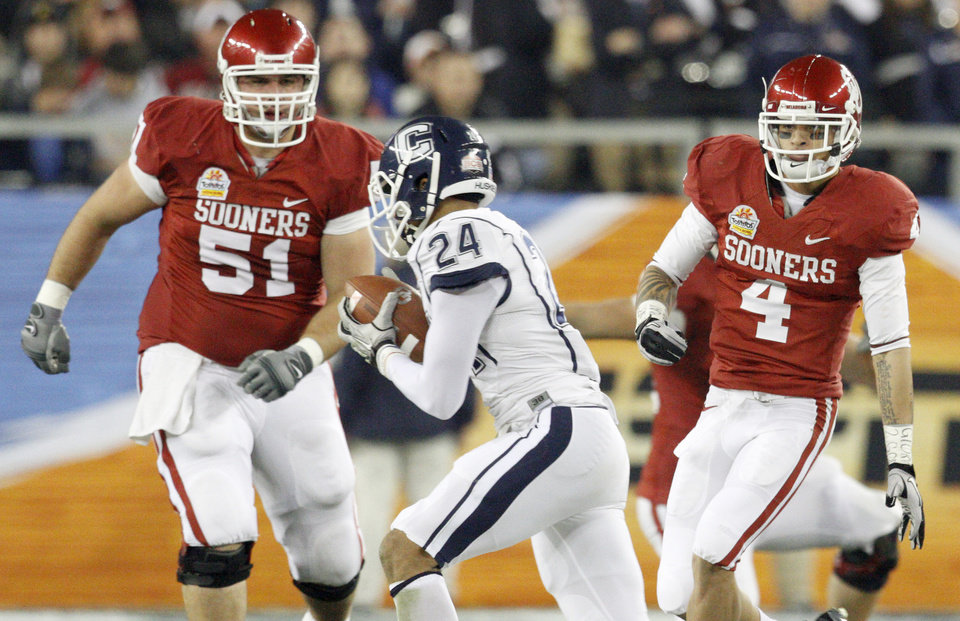 Photo - Oklahoma's Brian Lepak (51) and Oklahoma's Kenny Stills (4) watch as Connecticut's  Dwayne Gratz (24) for a touchdown during the Fiesta Bowl college football game between the University of Oklahoma Sooners and the University of Connecticut Huskies in Glendale, Ariz., at the University of Phoenix Stadium on Saturday, Jan. 1, 2011.  Photo by Bryan Terry, The Oklahoman