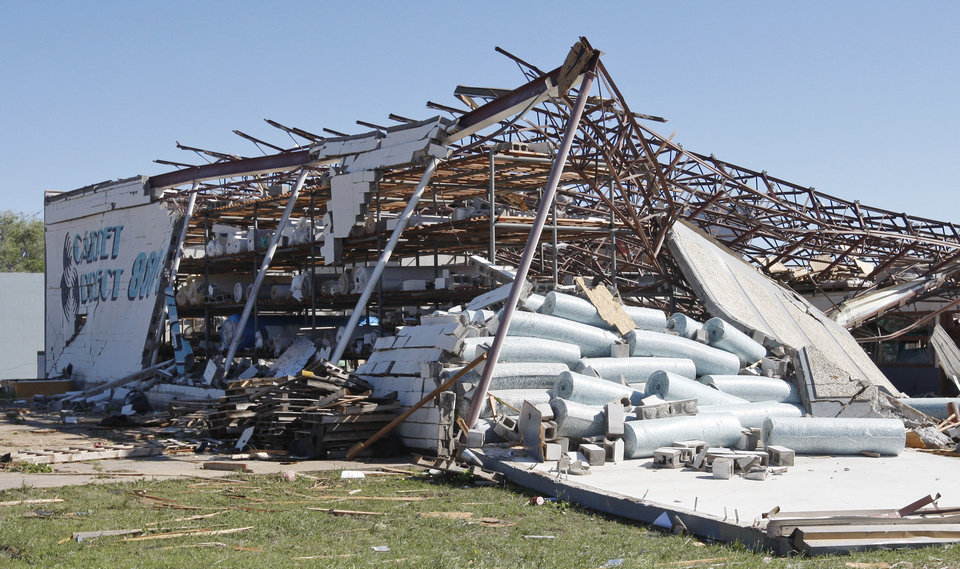 A carpet store is in ruins following a tornado in Woodward, Okla., Sunday, April 15, 2012. (AP Photo/Sue Ogrocki)